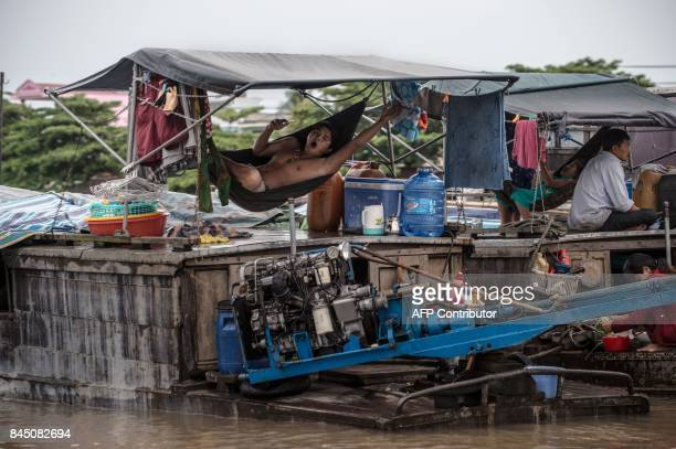 In this July 17, 2017 photograph, a resident of a house boat yawns as he swings on a hammock on the vessel in a canal off the Song Hau river at the...