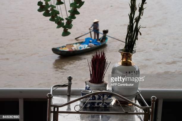In this July 17, 2017 photograph, a small shrine is seen on the deck of a river boat catering to tourists as a river vendor paddles past in search of...