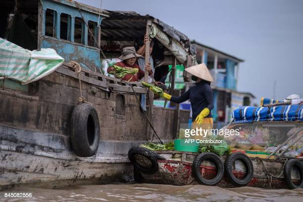 In this July 17 2017 photograph a vendor sells vegetables to a house boat owner in a canal off the Song Hau river at the floating Cai Rang market in...