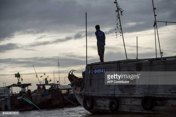 In this July 17 2017 photograph an onion vendor stands on the roof of his boat as he waits for customers in a canal off the Song Hau river in the...