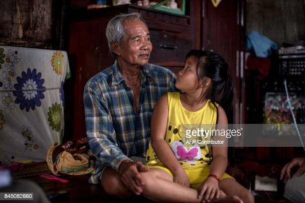 In this July 17 2017 photograph Nguyen Kim Ngan looks back at her seventyoneyearold grandfather Nguyen Van Ut a scales repairman as they sit inside...