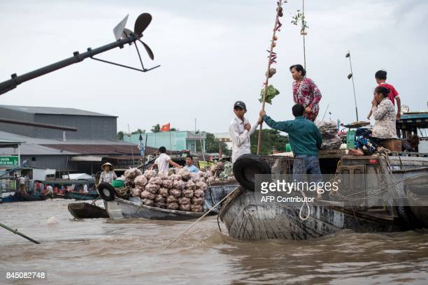 In this July 17 2017 photograph people stand on a boat from which its owners sell vegetables in a canal off the Song Hau river at the floating Cai...