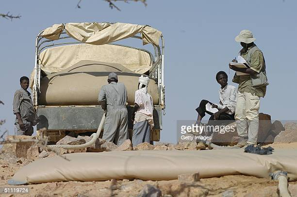 In this June 2004 handout people unload water from a Chad Red Cross Aid Convoy vehicle into ground bags at the top of a hill at Iridimi refugee camp...