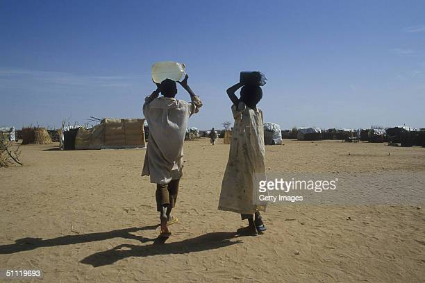 In this June 2004 handout two Sudanese refugees carry water to the Iridimi refugee camp in Chad. Efforts are currently underway July 27, 2004 to get...