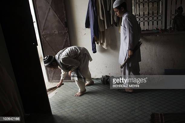 In this June 29, 2010 photograph, two Pakistani religious students sweep the dormitory of their Islamic seminary in Rawalpindi. According to...
