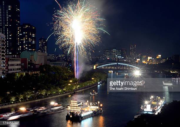 In this long exposure image fireworks explode at the Funatogyo the annual Tenjin summer festival boat parade along the Okawa river on July 25 2013 in...