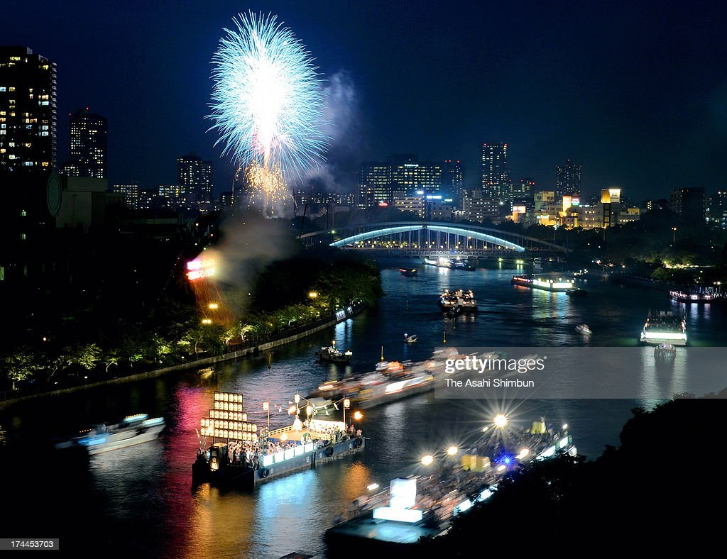 In this long exposure image, fireworks explode at the Funatogyo, the annual Tenjin summer festival boat parade along the Okawa river on July 25, 2013 in Osaka, Japan. The Tenjin Festival, one of the biggest festivals in Japan with over 1,000 years of history, is dedicated to Osakas prosperity and peoples peace. Hundreds of boats and ferries, decorated with lighted lanterns, join a procession at the end of the Tenjin summer festival each year.