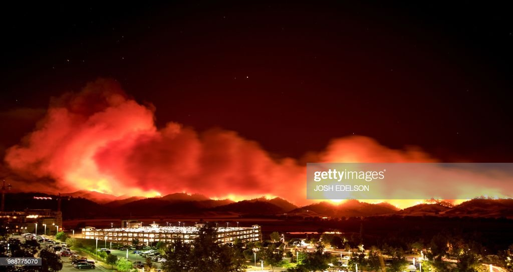 In this long exposure photo, fire burns behind Cache Creek Casino Resort near Guinda, California near on July 1, 2018. - Multiple wind-driven fires continue to whip through the region.