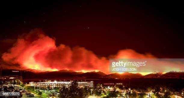 In this long exposure photo fire burns behind Cache Creek Casino Resort near Guinda California near on July 1 2018 Multiple winddriven fires continue...