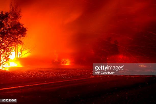 In this long exposure photograph embers fly off a burning house and truck in the Napa wine region in California on October 9 as multiple winddriven...