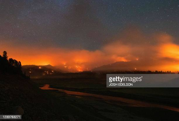 """In this long exposure photograph, flames surround a drought-stricken Shasta Lake during the """"Salt fire"""" in Lakehead, California early on July 2 as..."""