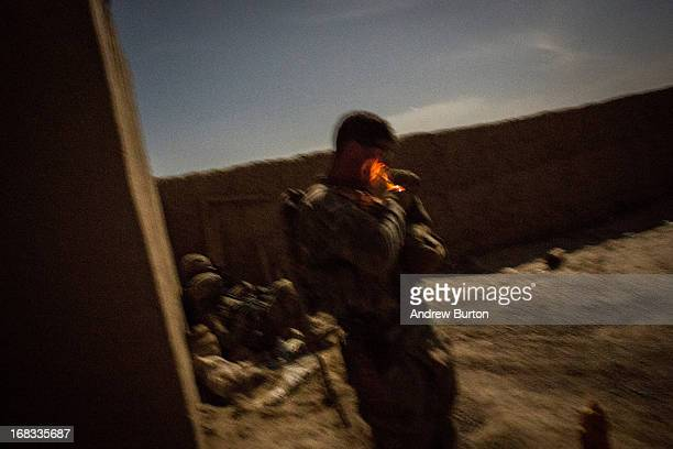 In this longexposure night photo a soldier with the United States Army's 3rd Battalion 41st Infantry Regiment lights a cigarette during a twoday...