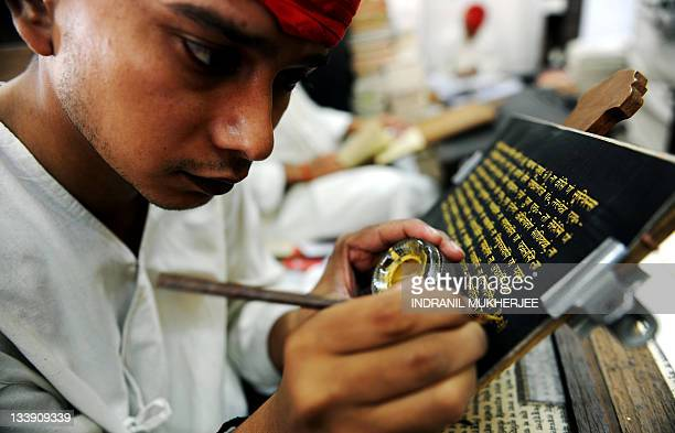 In this March 22 2010 photograph a Lehiyawriter artist replicates Jain scripture on jute paper with gold ink at a workshop in Mumbai Some 20odd...