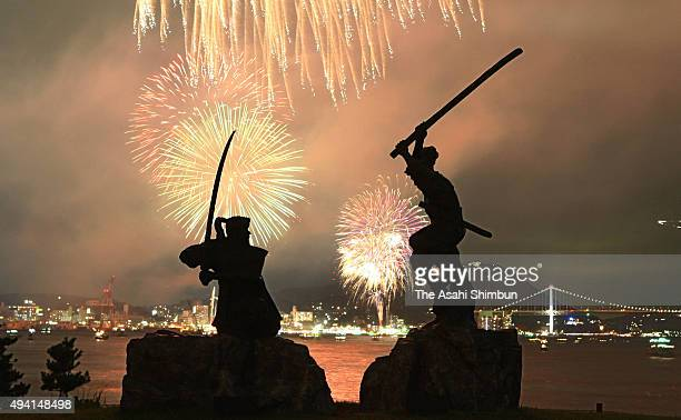 In this multiple exposure image fireworks explode while the silhouette of Battle of Ganryujima statue are seen during the Kanmon Strait Fireworks...