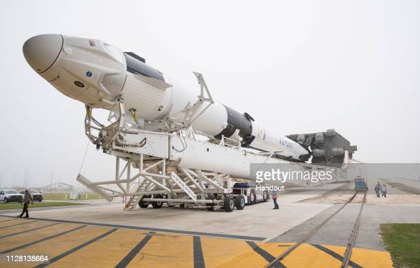 In this NASA handout, A SpaceX Falcon 9 rocket with the company's Crew Dragon spacecraft onboard is seen as it is rolled out of the horizontal...