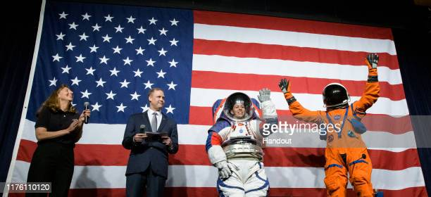 In this NASA handout Amy Ross a spacesuit engineer at NASAs Johnson Space Center left and NASA Administrator Jim Bridenstine second from left watch...