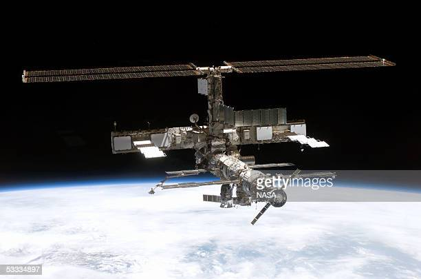 In this NASA handout, back dropped by the blackness of space and Earth?s horizon, this full view of the International Space Station is seen onboard...