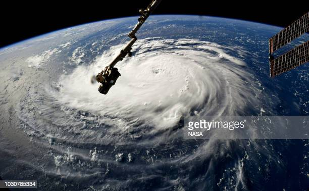 In this NASA handout image taken by Astronaut Ricky Arnold Hurricane Florence gains strength in the Atlantic Ocean as it moves west seen from the...