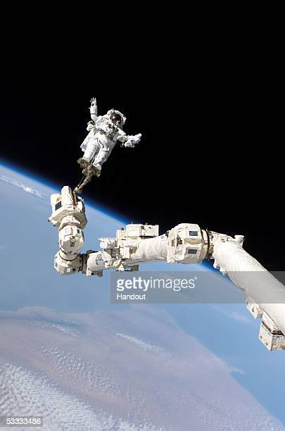 In this NASA handout mission specialist Astronaut Stephen K Robinson is anchored to a foot restraint on the International Space Station's Canadarm2...