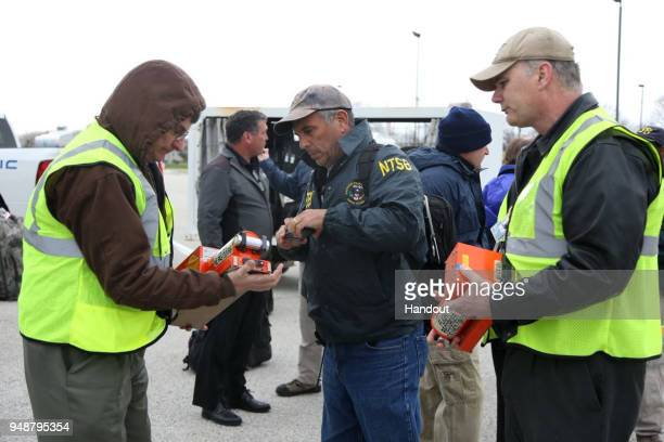 In this National Transportation Safety Board handout NTSB investigators carry the flight data recorders belonging Southwest Airlines Flight 1380...