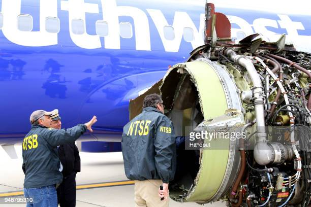 In this National Transportation Safety Board handout NTSB investigators examine damage to the CFM International 567B turbofan engine belonging...