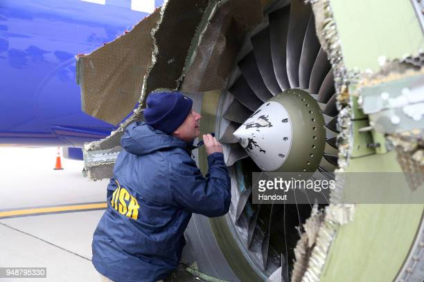In this National Transportation Safety Board handout NTSB investigator Jeanpierre Scarfo examines damage to the CFM International 567B turbofan...