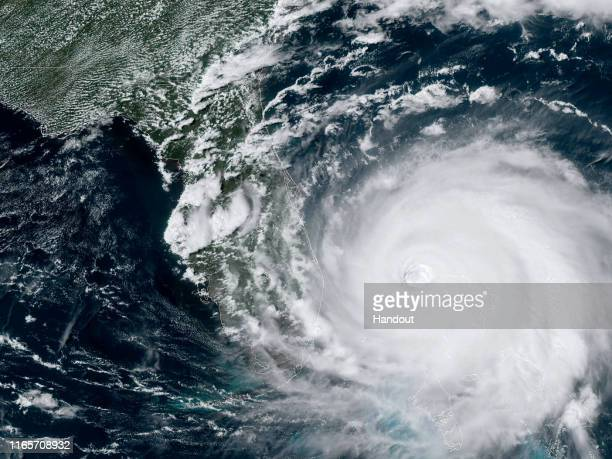 In this NOAA GOESEast satellite handout image Hurricane Dorian now a Cat 4 storm moves slowly past Grand Bahama Island on September 2 2019 in the...