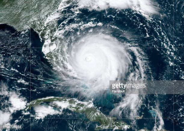 In this NOAA GOES-East satellite handout image, Hurricane Dorian, now a Cat. 4 storm, moves slowly past Grand Bahama Island on September 2, 2019 in...