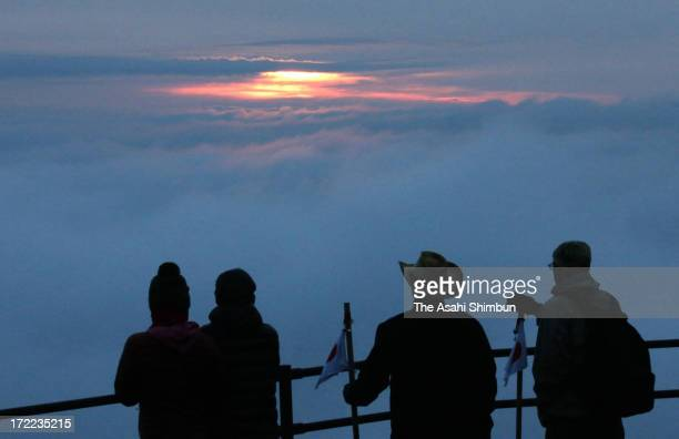 In this ong exposure image climbers using the Yoshidaguchi trail from the Yamanashi Prefecture side of Mount Fuji observe the sunrise from the eighth...