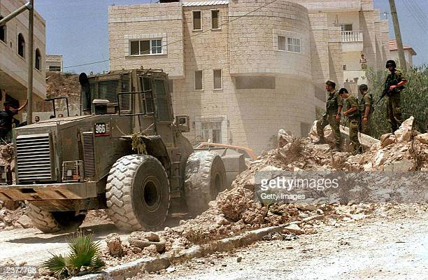 In this photo distributed by the Israeli Defense Forces Israeli troops stand guard as army bulldozer removes a military checkpoint August 7 2003...