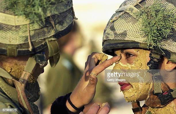 In this photo distributed by the Israeli Defense Forces May 23 a woman soldier is coated in mud as her infantry instructors' course learns about...