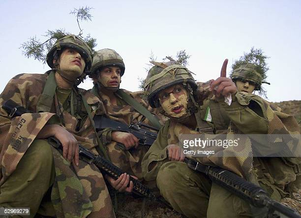 In this photo distributed by the Israeli Defense Forces May 23 woman soldiers are coated in mud and wear branches in their helmets as their infantry...
