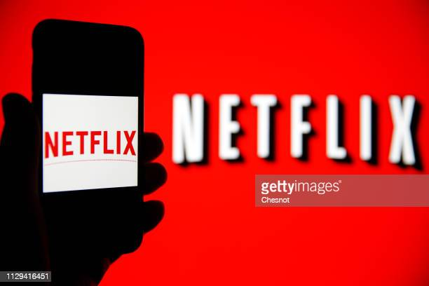 In this photo iIllustration, the Netflix logo is seen on the screen of an iPhone in front of a computer screen showing a Netflix logo on February 13,...