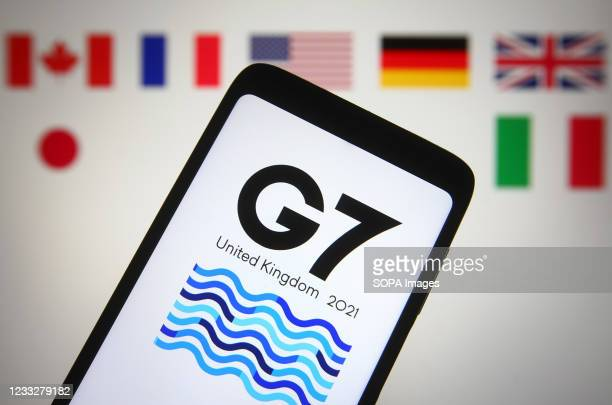 In this photo illustration, 47th G7 summit logo of the Group of Seven is seen on a smartphone screen in front of national flags of Canada, France,...