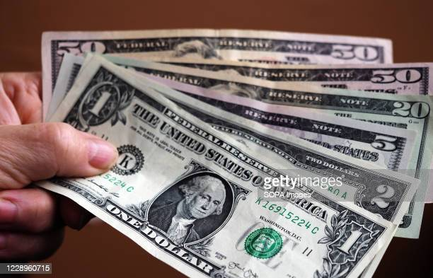 In this photo illustration a 1 dollar bill with various dollar bills.