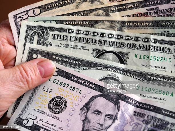 In this photo illustration a 5 dollar bill with various dollar bills.