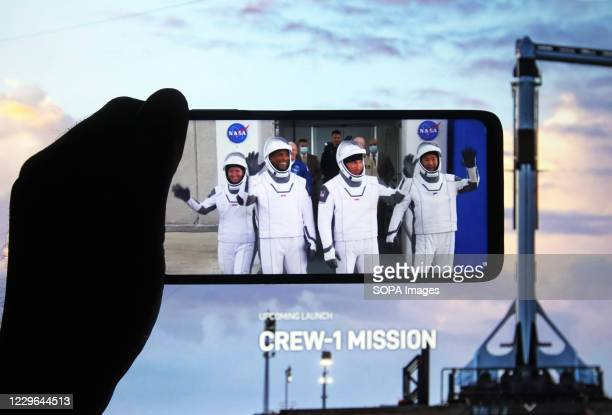 In this photo illustration a a screenshot of the webcast shows astronauts during the NASA SpaceX Crew-1 mission launch are seen on a smartphone...
