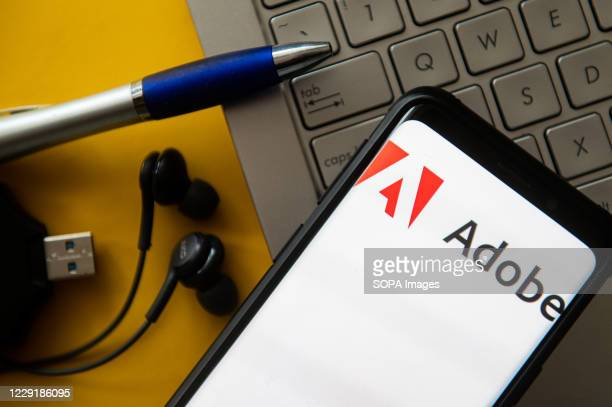 In this photo illustration a Adobe logo seen displayed on a smartphone.