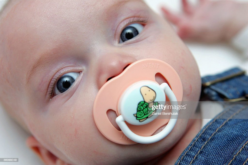 In this photo illustration a baby suckles a dummy whilst resting in her cot on December 09, 2005 in London, England. A recent US study has shown that cot deaths can be reduced by 90 percent if a baby sleeps with a dummy.