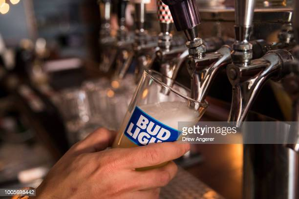 In this photo illustration, a bartender pours a Bud Light from a tap, July 26, 2018 in New York City. Anheuser-Busch InBev, the brewer behind...