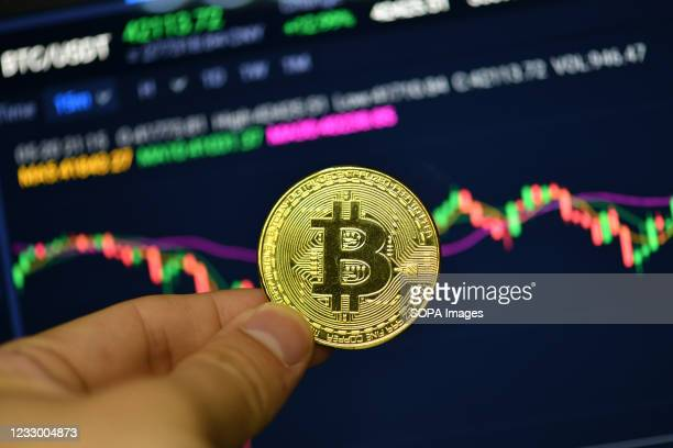 In this photo illustration a Bitcoin is seen on display with a Bitcoin price trend chart in the background.