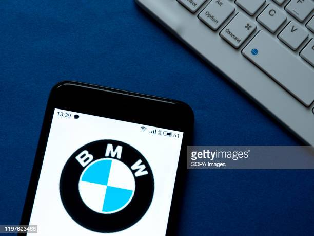 In this photo illustration a BMW logo seen displayed on a smartphone