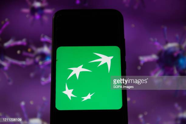 In this photo illustration a BNP Paribas logo displayed on a smartphone with a COVID 19 sample image in the background.