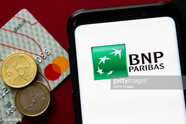 In this photo illustration a BNP Paribas logo seen displayed on a smartphone next to a debit card and two euro coins.