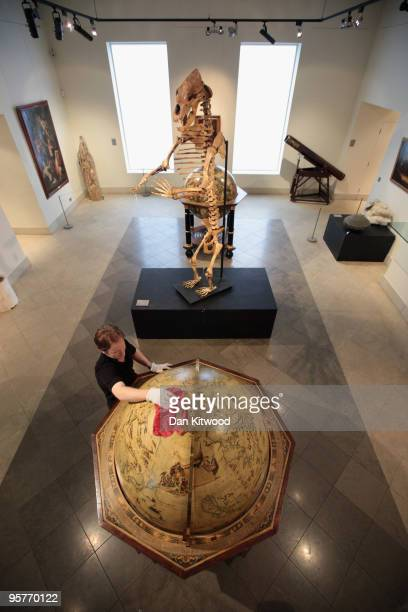 In this photo illustration a Bonhams employee cleans a 20th century Vincenzo Coronelli terrestrial globe which is for sale amongst a selection of...