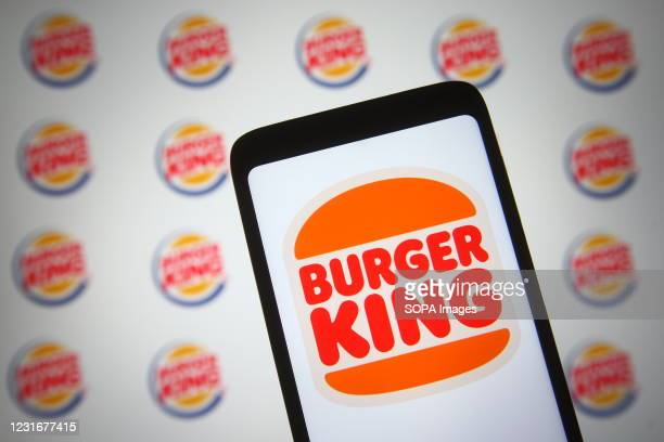 In this photo illustration a Burger King logo of a US chain of hamburger fast food restaurants is seen on a smartphone and a pc screen.