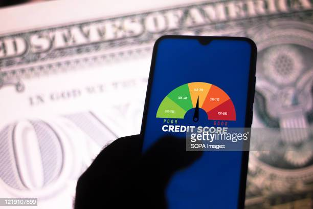 In this photo illustration a businessman holds his smartphone showing a graph with the credit score