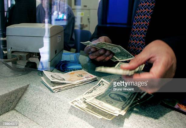 In this photo illustration a cashier at a Bureau de Change counts out American Dollars on April 17 2007 in London The British Pound has hit the two...