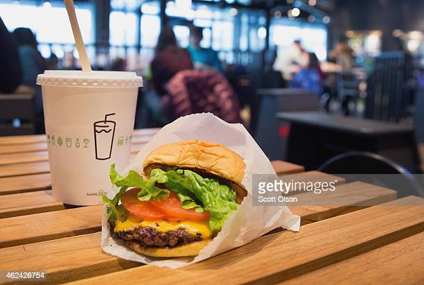 In this photo illustration a cheeseburger and drink is served up at a Shake Shack restaurant on January 28, 2015 in Chicago, Illinois. The burger...