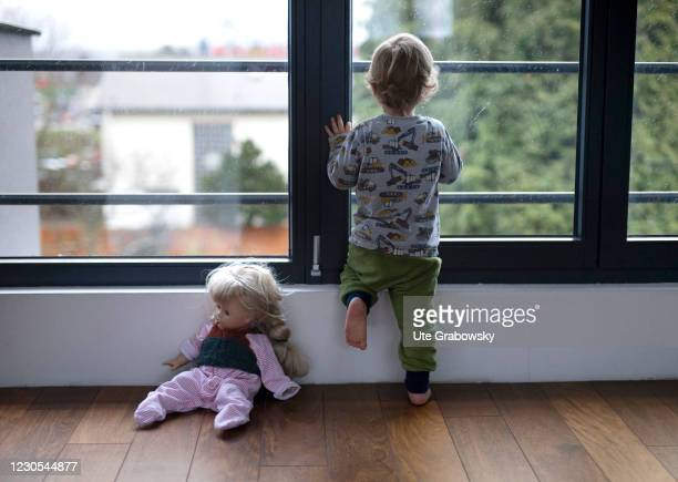 In this photo illustration a child looks out of the window in times of corona pandemic on January 12, 2021 in Bonn, Germany.